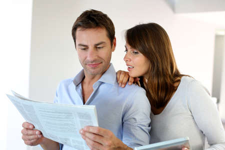 Couple reading news on newspaper and internet Stock Photo - 15849432