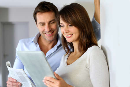 Couple at home reading news on newspaper and internet photo