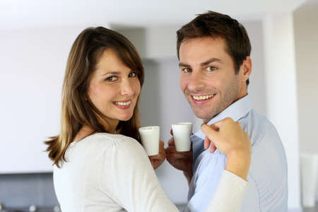 Cheerful couple holding cups of coffee photo
