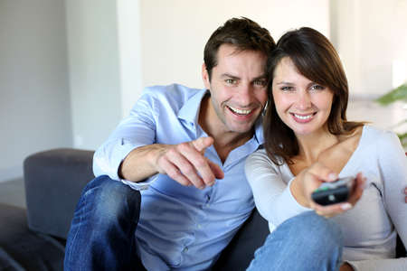 tv set: Couple sitting in couch choosing tv program