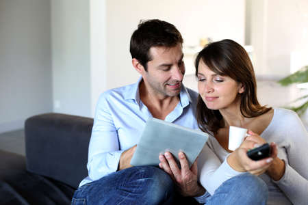 couple on couch: Couple sitting in couch choosing tv program