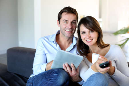 Couple sitting in couch choosing tv program photo