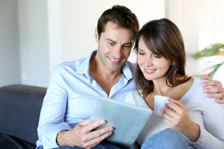 attractive couch: Couple in sofa websurfing on internet with tablet