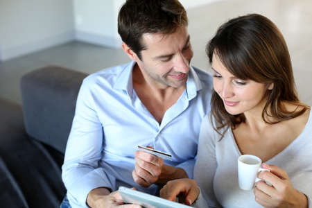 Mature couple at home using credit card to shop online photo