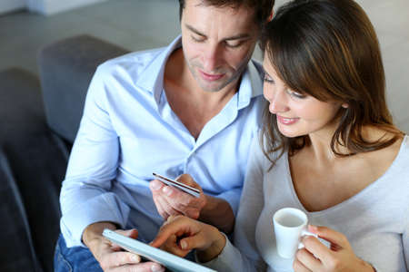 home shopping: Mature couple at home using credit card to shop online Stock Photo