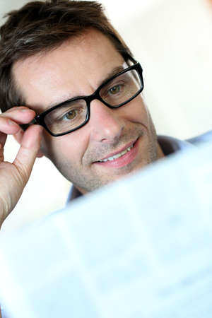 Man with eyeglasses reading newspaper Stock Photo - 15849228