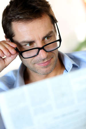 Man with eyeglasses reading newspaper photo