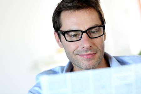 40 years old man: Man with eyeglasses reading newspaper
