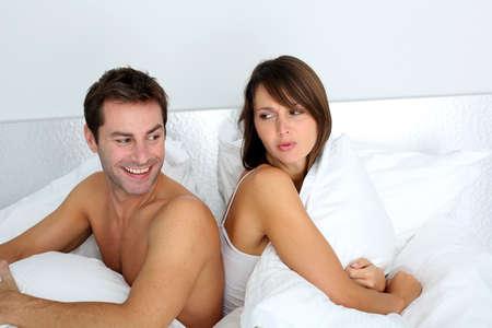 pareja discutiendo: Pareja sentados espalda con espalda en la cama, con el argumento Foto de archivo