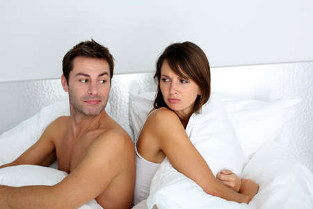 Couple sitting back to back in bed, arguing photo