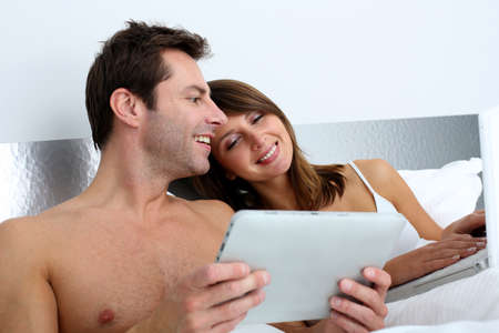 Couple in bed websurfing on internet photo