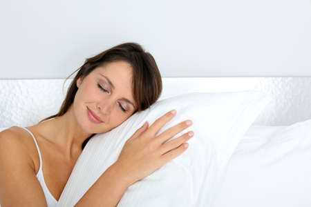 silent night: Woman feeling good asleep in bed Stock Photo