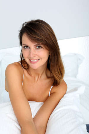35 years old: Portrait of attractive brunette girl sitting in bed