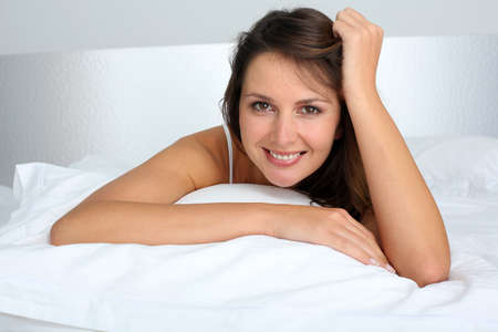 Portrait of beautiful woman laying in bed photo