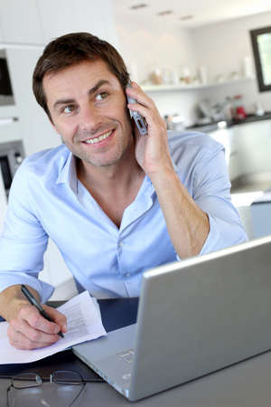 Home office worker talking on mobile phone Stock Photo - 15849358