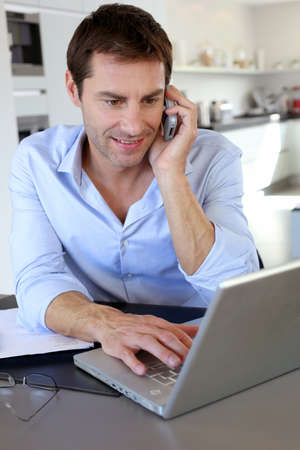 telephone salesman: Home office worker talking on mobile phone