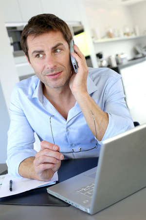 teleworker: Home office worker talking on mobile phone
