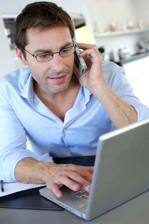 Home office worker talking on mobile phone Stock Photo - 15849355