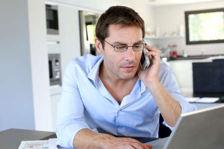 Home office worker talking on mobile phone Stock Photo - 15849284