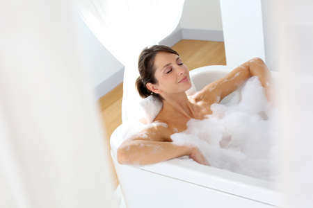 bathtubs: Beautiful woman relaxing in bathtub Stock Photo
