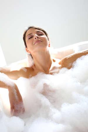 lying in bathtub: Beautiful woman relaxing in bathtub Stock Photo