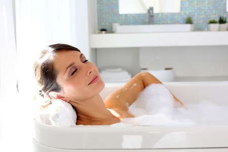 resting: Beautiful woman relaxing in bathtub Stock Photo