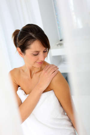 towels luxury: Beautiful woman in bathroom using cosmetics