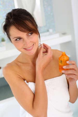 35 years old: Beautiful woman in bathroom using cosmetics