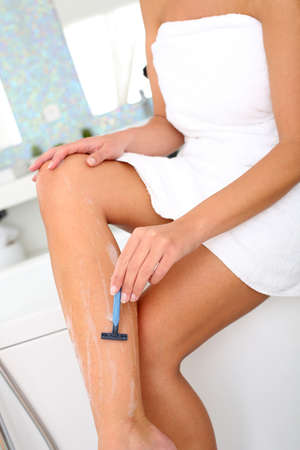 Woman in bathroom shaving her legs photo