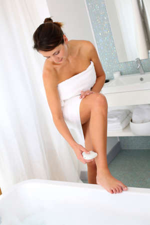 epilator: Woman shaving her legs in bathroom Stock Photo