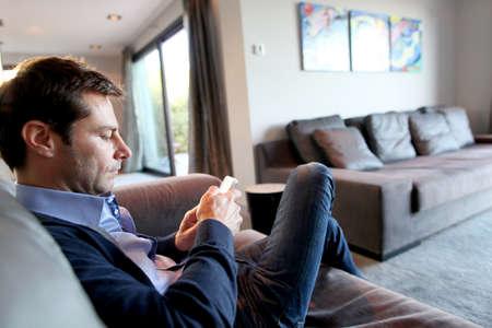 sending: Hombre env�o de mensajes cortos con el tel�fono inteligente Foto de archivo