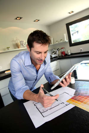 Man looking at house blueprint and choosing paint colours photo