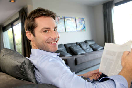 Man relaxing in sofa with newspaper photo