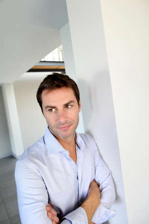 40 years old man: Man leaning on wall with arms crossed