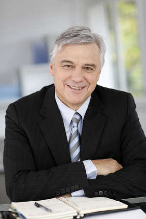 senior business: Portrait of smiling senior businessman with arms crossed Stock Photo