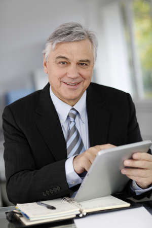 Portrait of senior businessman in office using tablet photo