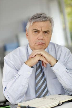 hombre preocupado: Hombre de negocios mayor serio delante de cliente
