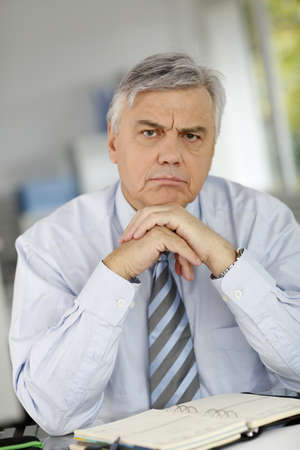Senior businessman being serious in front of client photo