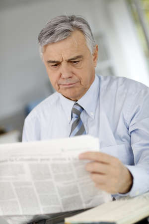 Senior businessman reading newspaper with puzzled look photo
