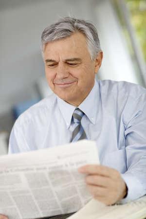 Portrait of senior businessman reading newspaper photo