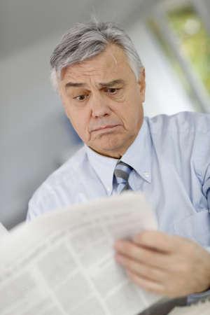 inquiring: Senior businessman reading news with inquiring look
