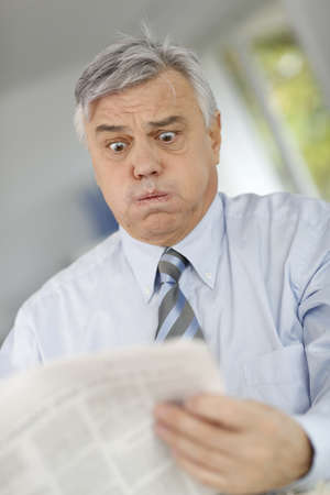 horrified: Senior businessman reading newspaper with horrified look Stock Photo