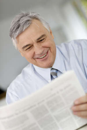 Smiling businessman reading newspaper in office photo
