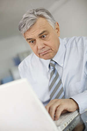 Senior businessman working on laptop with surprised look photo