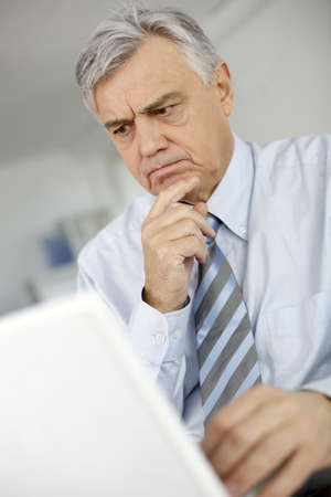 Senior man with puzzled look in front of laptop photo