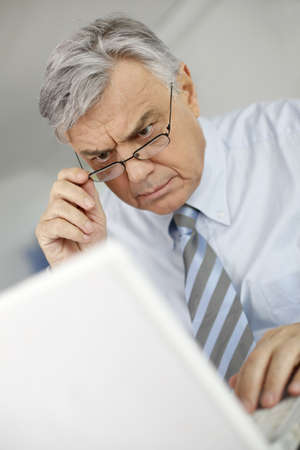Portrait of businessman with perplexed look in front of laptop photo