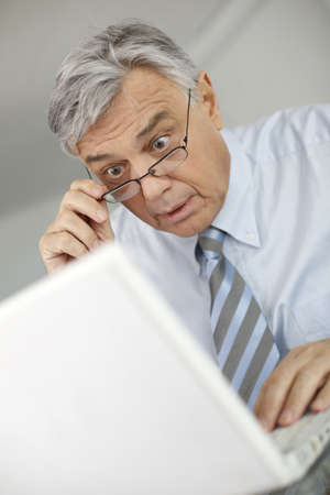 shocked: Portrait of businessman with suprised look in front of laptop Stock Photo