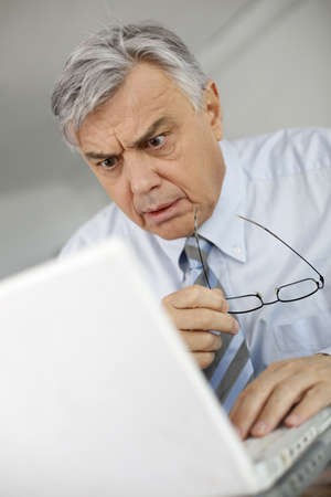 Portrait of businessman with suprised look in front of laptop photo