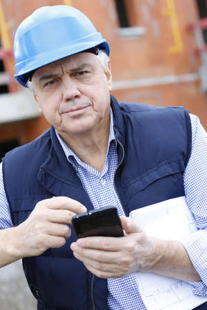Entrepreneur on construction site using smartphone Stock Photo - 16320871