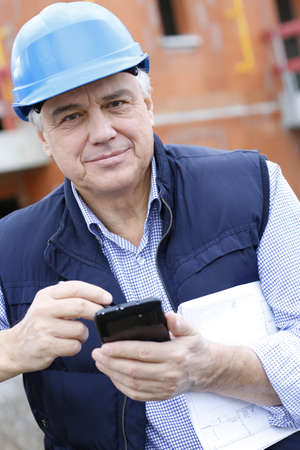 site manager: Entrepreneur on construction site using smartphone